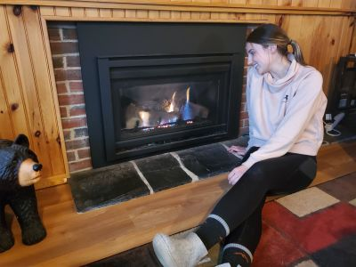 Christina in front of her propane fireplace.